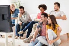 Amigos felices con palomitas que ven la TV en casa Foto de archivo
