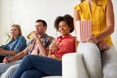 Amigos felices con palomitas que ven la TV en casa Imagenes de archivo