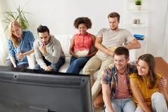 Amigos felices con palomitas que ven la TV en casa Fotografía de archivo