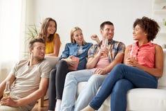 Amigos felices con palomitas y cerveza en casa Fotos de archivo
