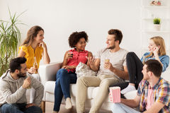 Amigos felices con palomitas y cerveza en casa Fotografía de archivo