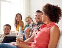Amigos felices con palomitas y cerveza en casa Imágenes de archivo libres de regalías