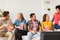 Amigos felices con palomitas y el telecontrol de la TV en casa Imágenes de archivo libres de regalías