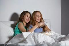 Amigos felices con palomitas y la TV de observación en casa Fotografía de archivo