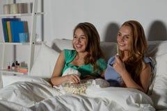 Amigos felices con palomitas y la TV de observación en casa Imagen de archivo libre de regalías