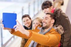 Amigos felices con PC de la tableta en pista de patinaje Fotografía de archivo