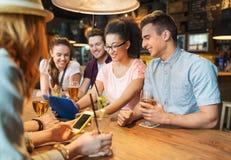 Amigos felices con PC de la tableta y bebidas en la barra Fotografía de archivo libre de regalías