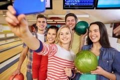 Amigos felices con smartphone en club de los bolos Fotografía de archivo libre de regalías