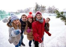 Amigos felices con smartphone en pista de patinaje de hielo Imagen de archivo libre de regalías