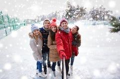 Amigos felices con smartphone en pista de patinaje de hielo Fotografía de archivo libre de regalías