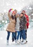 Amigos felices con smartphone en pista de patinaje de hielo Fotografía de archivo