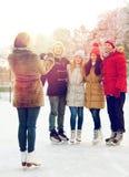 Amigos felices con smartphone en pista de patinaje de hielo Fotos de archivo libres de regalías