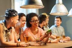 Amigos felices con smartphone y bebidas en la barra Fotografía de archivo libre de regalías