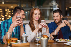 Amigos felices con smartphones en el restaurante Fotos de archivo