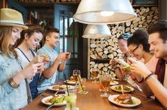 Amigos felices con smartphones que representan la comida Fotografía de archivo