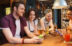 Amigos felices con smartphones y bebidas en la barra Fotos de archivo libres de regalías