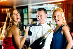 Amigos felices con un champán de la botella en la barra Imagen de archivo libre de regalías
