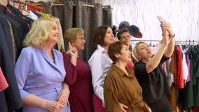 Amigos felices de la mujer que presentan para el selfie por el teléfono móvil en tienda de ropa Mujeres mayores alegres que prese almacen de metraje de vídeo