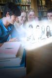 Amigos felices de la universidad que miran las fotos en interfaz futurista Foto de archivo