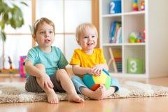 Amigos felices de los niños pequeños que se sientan en piso en guardería Foto de archivo