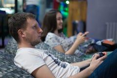 Amigos felices de los pares que juegan a los videojuegos con la palanca de mando que se sienta en silla del puf Fotos de archivo libres de regalías