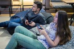 Amigos felices de los pares que juegan a los videojuegos con la palanca de mando que se sienta en silla del puf Imagen de archivo libre de regalías