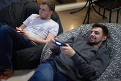 Amigos felices de los pares que juegan a los videojuegos con la palanca de mando que se sienta en silla del puf Fotos de archivo