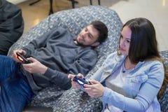 Amigos felices de los pares que juegan a los videojuegos con la palanca de mando que se sienta en silla del puf Foto de archivo