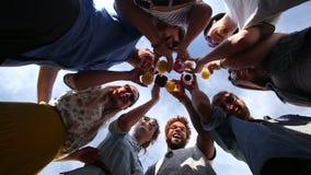 Amigos felices del Grupo de los Ocho que consideran abajo la cámara y tostar metrajes
