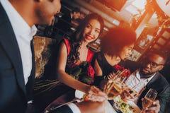 Amigos felices del grupo que disfrutan de fechar en restaurante imagen de archivo libre de regalías