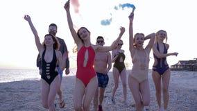 Amigos felices en bañadores con la granada de humo que disfrutan de vacaciones de verano a lo largo de la orilla del mar metrajes