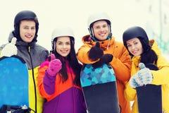 Amigos felices en cascos con las snowboard Fotografía de archivo