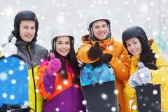 Amigos felices en cascos con las snowboard Foto de archivo libre de regalías