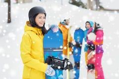 Amigos felices en cascos con las snowboard Imagenes de archivo