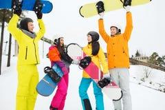 Amigos felices en cascos con las snowboard al aire libre Fotografía de archivo