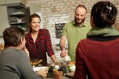 Amigos felices en cocina Foto de archivo libre de regalías