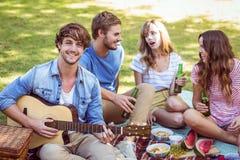 Amigos felices en el parque que tiene comida campestre Imagen de archivo libre de regalías