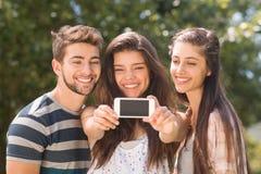 Amigos felices en el parque que toma el selfie Fotografía de archivo