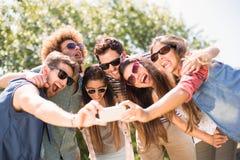 Amigos felices en el parque que toma el selfie Foto de archivo libre de regalías