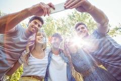 Amigos felices en el parque que toma el selfie Imagen de archivo libre de regalías