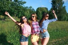 Amigos felices en el parque en un día soleado El retrato de la forma de vida del verano de tres mujeres del inconformista disfrut imagenes de archivo