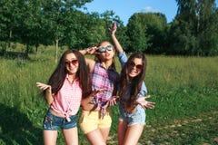 Amigos felices en el parque en un día soleado El retrato de la forma de vida del verano de tres mujeres del inconformista disfrut fotografía de archivo libre de regalías