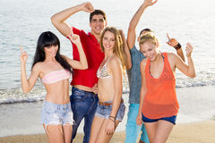 Amigos felices en equipos del verano en la playa Imágenes de archivo libres de regalías