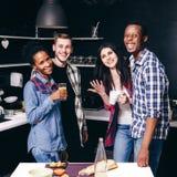 Amigos felices en la cocina, dos pares interraciales Foto de archivo libre de regalías