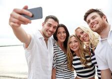 Amigos felices en la playa y el selfie el tomar Fotografía de archivo
