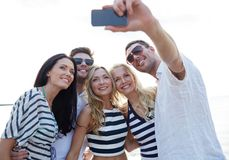 Amigos felices en la playa y el selfie el tomar Fotografía de archivo libre de regalías