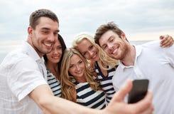 Amigos felices en la playa y el selfie el tomar Imagenes de archivo