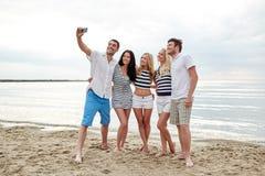 Amigos felices en la playa y el selfie el tomar Imagen de archivo libre de regalías