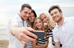 Amigos felices en la playa y el selfie el tomar Imágenes de archivo libres de regalías