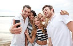 Amigos felices en la playa y el selfie el tomar Foto de archivo libre de regalías